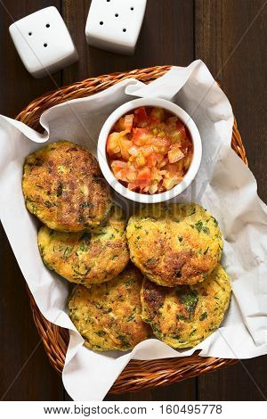 Zucchini couscous and parsley fritters with cooked tomato and onion salsa in basket photographed overhead with natural light (Selective Focus Focus on the top of the fritters and the salsa)