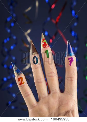 Four fingers with imprinted 2017 date decorated with paper cones over dark blue background with streamers
