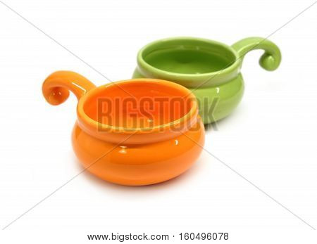 Two small color clay empty cocotte isolated on white diagonal view closeup