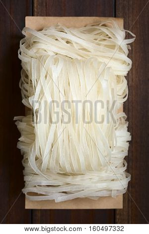 Raw rice flour noodles photographed overhead on dark wood with natural light (Selective Focus Focus on the top of the noodles)