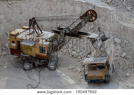 Excavator and dump truck working and extracting the chalk in a quarry. Excavator pours chalk into box of truck