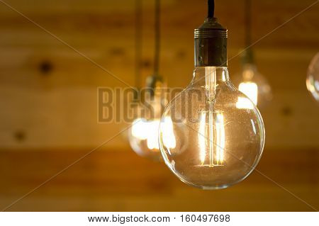 Closeup image of a filament light bulb turned on.