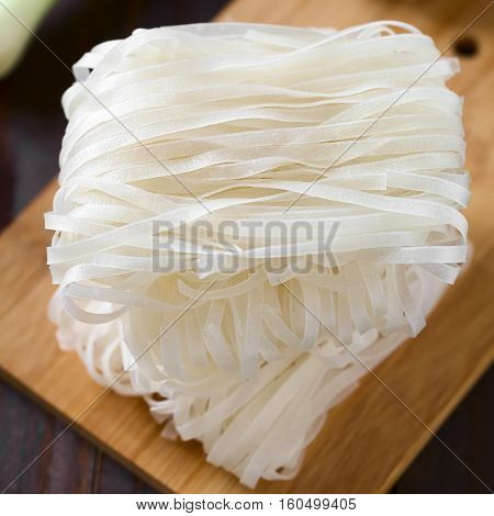 Raw rice flour noodle bundles piled on wooden board photographed with natural light (Selective Focus Focus in the middle of the top bundle)