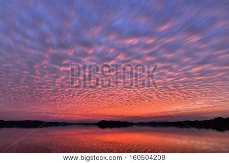 Beautiful sunset sky with colourful altocumulus clouds with reflexion over the lake natural background photo texture