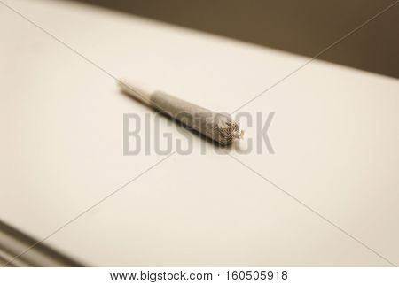 Rolled joint, cigarette, or spliff on counter top.