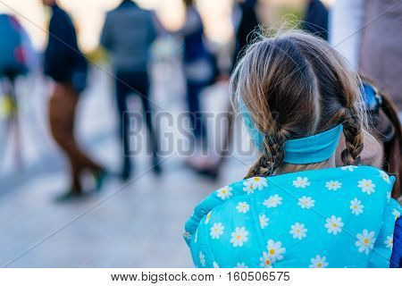 One little girl in anonymous crowd of people