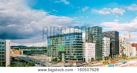 Oslo, Norway. The Night Panoramic View Of Contemporary District Of Black And White High-Rised Buildings In The Center Of City In Bright Illumination In Summer Evening, Blue Sky Background, Copyspace.