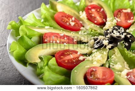 Slices of avocado on fresh salad leaves with cherry tomatoes grated cheese and olives selective focus