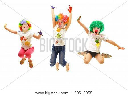 Jumping children wearing clowns costumes on white