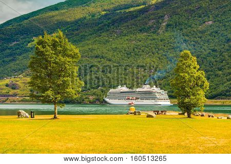 Tourism vacation and travel. Mountains landscape and big cruise ship on fjord Sognefjord in Flam Norway Scandinavia.