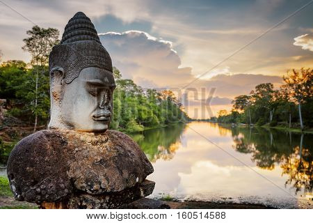 Stone Asura And Sunset Over Moat Surrounding Angkor In Cambodia
