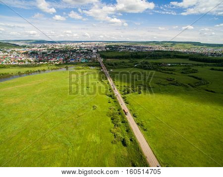 Cow, road, green near of border of Tatar and Bashkir state. Aerial view. Russia