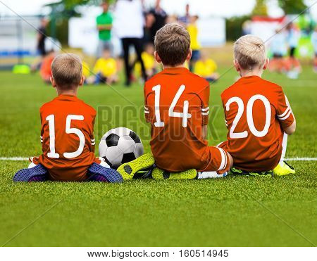 Football Game for Kids. Young Boys Soccer Players Athletes. Children Football Players at Match with Ball. Soccer Bench of Youth Team. Footballers in Orange Sportswear