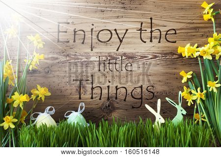 Wooden Background With English Quote Enjoy The Little Things. Easter Decoration Like Easter Eggs And Easter Bunny. Sunny Yellow Spring Flower Narcisssus With Gras. Card For Seasons Greetings