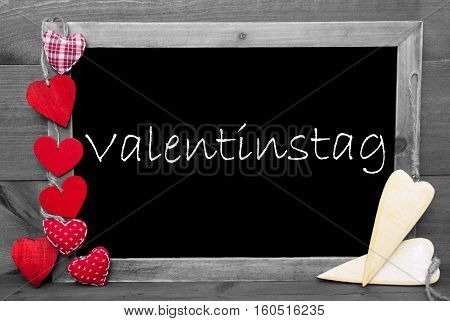 Chalkboard With German Text Valentinstag Means Valentines Day. Red Hearts. Wooden Background With Vintage, Rustic Or Retro Style. Black And White Image With Colored Hot Spots.