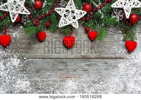 Christmas background with decorations velvet hearts and fir tree on wooden board covered with snow with copy space. top view