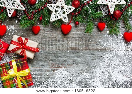 Christmas background with fir tree decorations gift boxes and velvet hearts on rustic wooden background covered with snow. top view