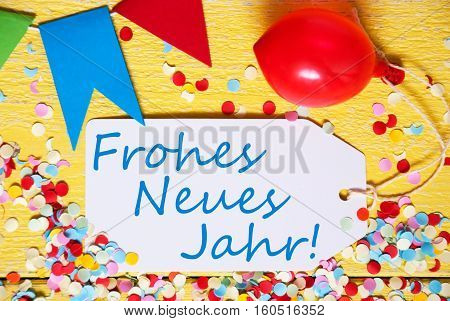 White Label With German Text Frohes Neues Jahr Means Happy New Year. Close Up Of Party Decoration Like Streamer, Confetti And Balloon. Flat Lay Or Top View. Yellow Wooden Background