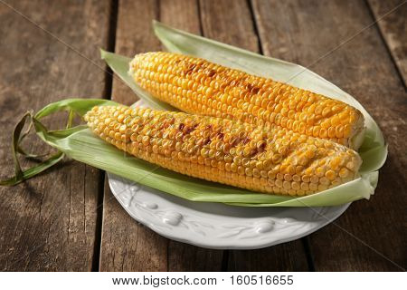 Plate with tasty grilled corncobs on wooden table, close up view