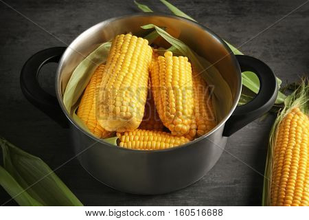 Tasty boiled corncobs in saucepan on kitchen table