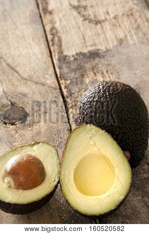 Ripe halved and whole avocado pear on a rustic wooden table ready to be served as a salad ingredient high angle view with copy space