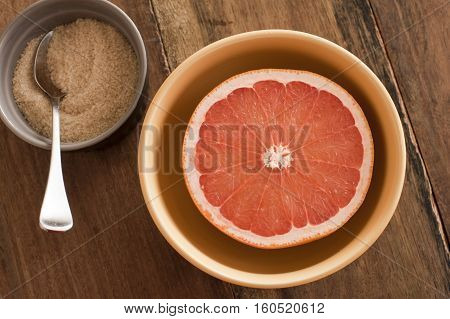 Fresh halved pink grapefruit served with an accompanying bowl of sugar for a healthy breakfast rich in Vitamin C