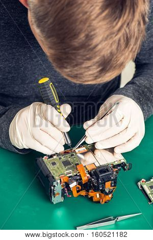 Close up hand of a technician repairing digital camera