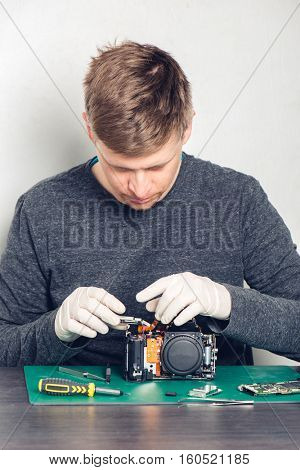 Technician in latex gloves repairing digital camera in a service laboratory