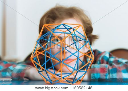 Coloured three-dimensional model of geometric solid against the background of the young man's face defocused. Selective focus on foreground.