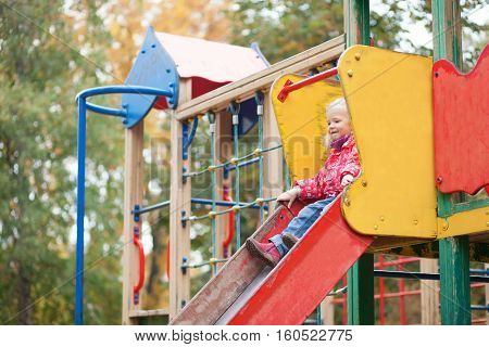 Adorable Little Girl Preparing To Slither From A Slide