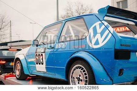 STUTTGART GERMANY - DEC 2 2016: Blue Volkswagen GTI racing car on a trailer on the traffic jam in the city of Stuttgart