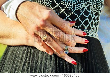 people holidays engagement and love concept - close up of engaged couple holding hands with diamond ring over holidays lights background