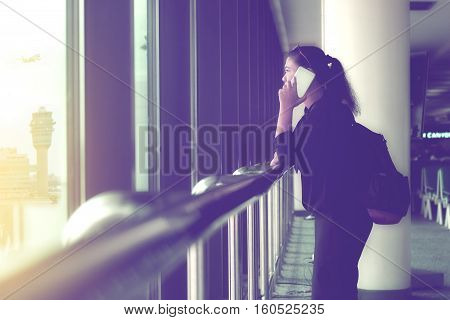 business woman talking on the phone while waiting for her flight