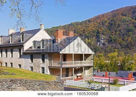 Houses on the street of historic town in Harpers Ferry National Historical Park West Virginia USA. The town in autumn colors with Blue Ridge Mountains on background.