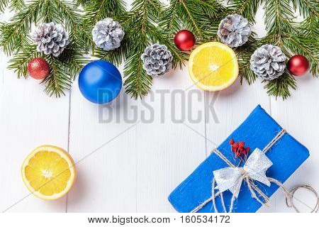 Christmas New Year composition with tangerines, cones, nuts, wicker basket and fir branches in rustic style on old wooden background, selective focus, Background new year, fir, gift, cones, orange, blue ball, red background, snow, ,