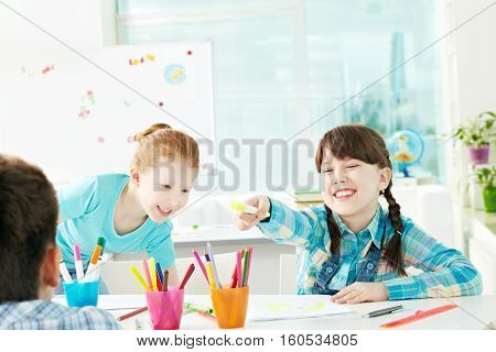 Two little girls sneering at their classmate at school