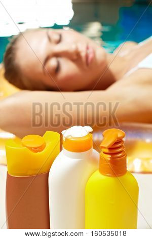 Close-up of suntan lotion with woman sunbathing on the background
