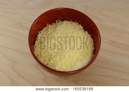 Grated shredded parmesan cheese in red bowl on table