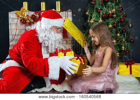 Santa Claus and a girl in a dress. Christmas Scenes. The child opens the gift and looks inside