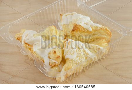 Apple turnovers with icing in plastic bakery packaging with one missing already