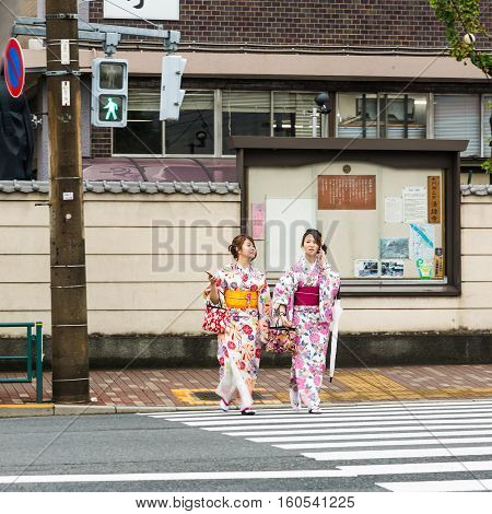 TOKYO JAPAN - 08 OCTOBER 2016 - Unidentified Japanese pedestrians in their kimono dress walk across the road at pedestrian crossing while the signal goes green.