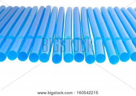 blue tubules for cocktail are put in a row on a white background