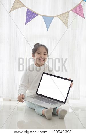 Happy Asian girl showing laptop screen in decorated room with pastel triangle party flag, High key process