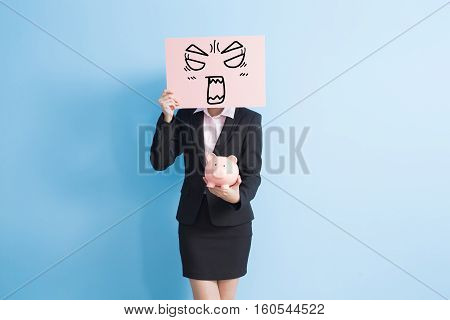 businesswoman take angry billboard and show piggy bank to you isolated with blue background
