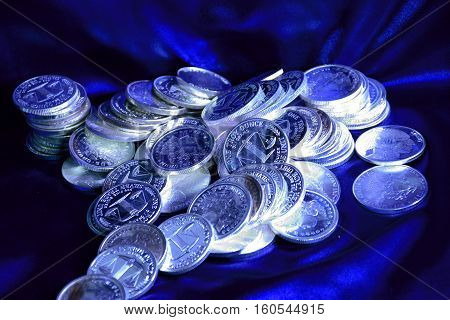 one ounce silver coins with blue background some in a pile some stacked