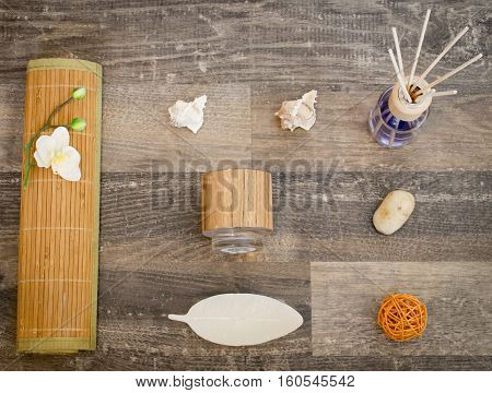 On a surface of wood are a bamboo mat with an orchid a tea light holder shells stones a candle in the shape of a leaf a woven ball and a container with fragrance oil