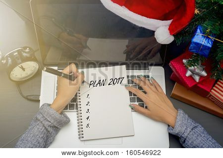 business woman hand writing Plan 2017 text on note book. concept office christmas and happy new year to do list 2017.