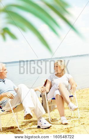 Senior couple resting on beach in chaise lounges