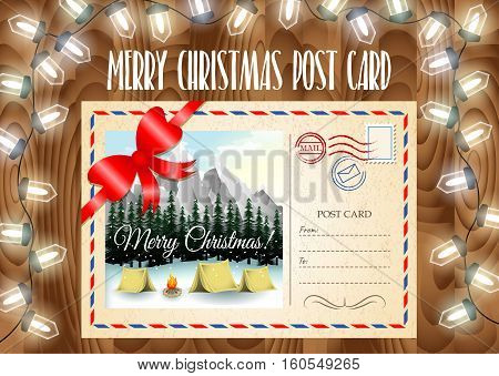 Merry Christmas post card design. Merry Christmas post card on the wood table with garland lights. Camping in mountains landscape.