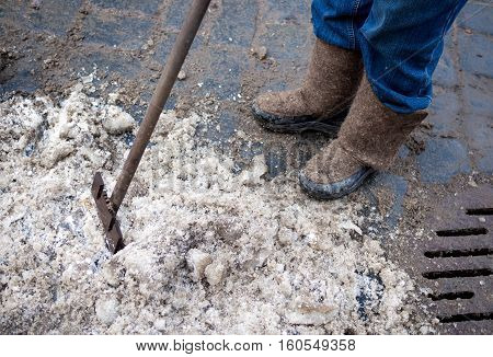 Janitor cleans the ice on the street with a crowbar